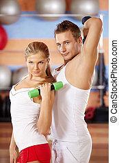 Dumb-bells - Pair of sportsmen with dumbbells in hands in...