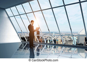 businessman with laptop in white loft office