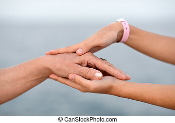 Child holding mother hand with tender