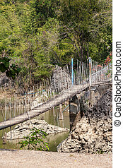suspension bridge - above the water between two rocks hangs...