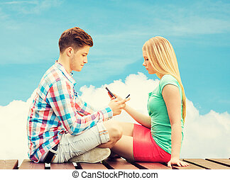 couple with smartphones sitting on bench over sky - summer,...