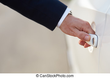 Hand of businessman in formal wear opening a car door