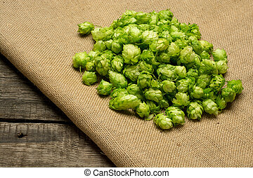 Fresh green hops on burlap background Top view - Fresh green...