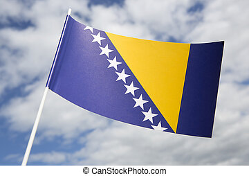 Bosnia Herzegovina flag in front of a blue sky