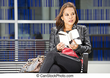 Woman, reading a book making eye contact - Woman, siting on...
