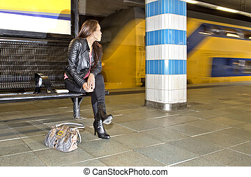 Woman looking at a passing train - Woman looking over her...