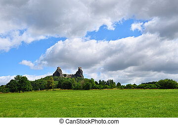 Green grassfield with medieval castle ruins under cloudy sky