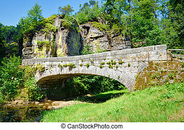 Old stone bridge over a small rivulet in summer season