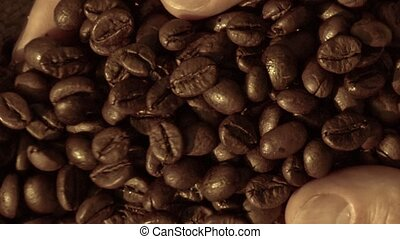 Fresh roasted coffee beans pouring out of cupped hands into...
