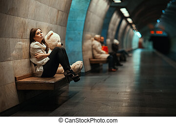 Sad woman sitting on a bench in the subway. Away blurred...
