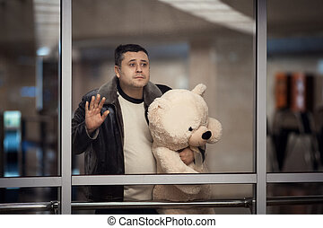 Man holding toy bear and looking sadly into the distance. -...