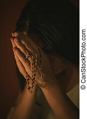 Woman praying - Unrecognizable woman with a rosary praying...