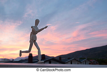 Wooden figure mannequin running at sunset
