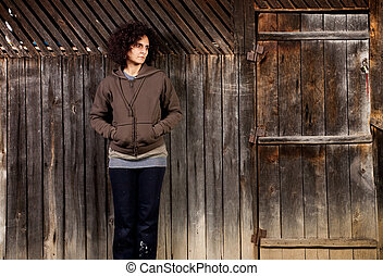 Woman standing near wooden wall