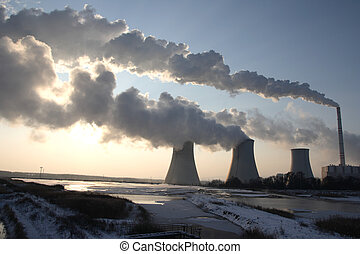 View of coal power plant against sun and huge fumes