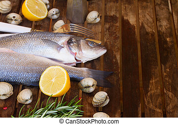 Seabass - Two Seabass raw fish with shellfish and spices on...