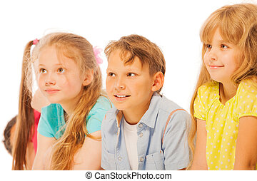 Four kids sitting in a row smiling and listening - Group of...