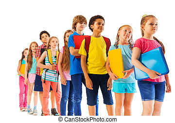 Kids standing in the line holding textbooks - Group of...