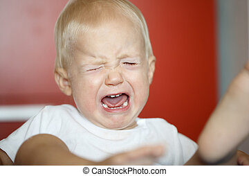 Small, crying and raging toddler having a temper tantrum -...