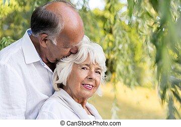 Elder marriage hugging affectionately in city park
