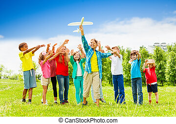 Kid holding white airplane toy and children behind - View of...