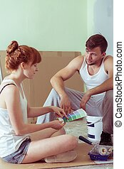 Young couple redecorating house and choosing color for walls