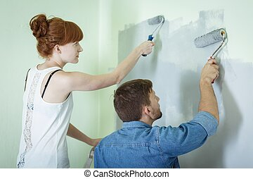 Couple painting wall together - Couple redecorating house...