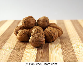 Walnuts - Closeup of walnuts over an alternate colors wooden...