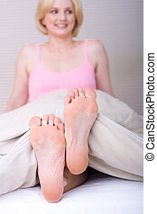 feet - a woman smiling with her feet sticking out from the...