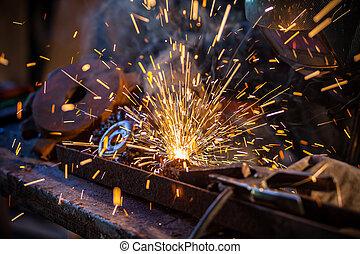 Welder in action. Low depth of focus - Close-up of welder...