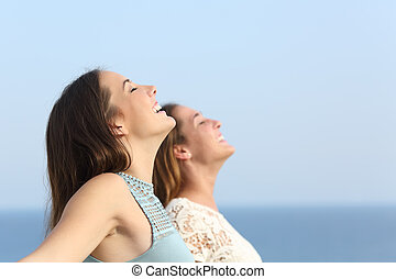 Two girls breathing deep fresh air on the beach - Two girls...