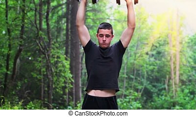 Teenager exercising with dumbbells for shoulders