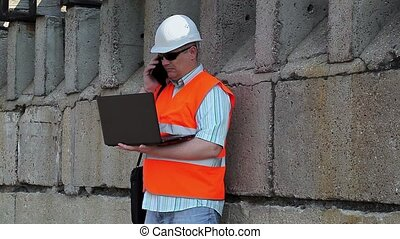 Engineer using phone and laptop near wall