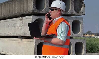 Construction Engineer using phone and laptop