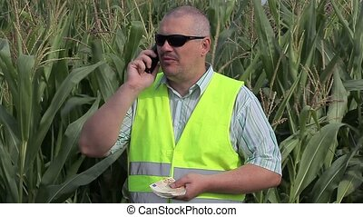 Farmer with smartphone and money on corn field