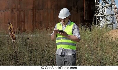 Thoughtful engineer using tablet PC near tanks