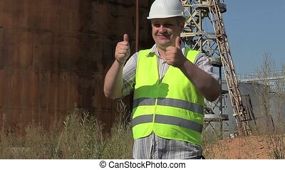 Happy Engineer showing thumbs up near to the tanks