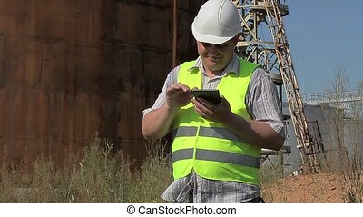 Happy Engineer using tablet PC near to the tanks