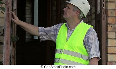 Building inspector near to the broken door