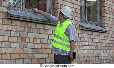 Building inspector check the broken window