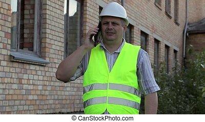 Building inspector talking on smartphone