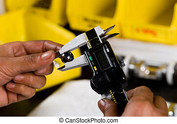 Hands Holding Measuring Device - Image of hands holding a...