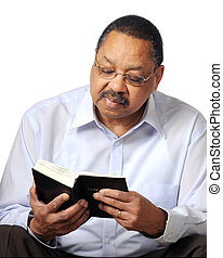 Studying Gods Word - A black senior man reading a paperback...