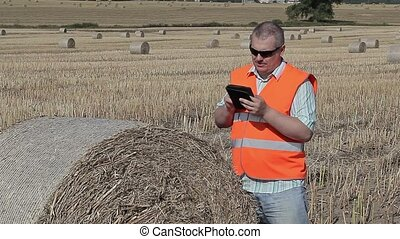 Farmer with tablet PC near hay bales on field in summer