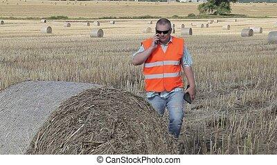 Farmer talking on smartphone near hay bales