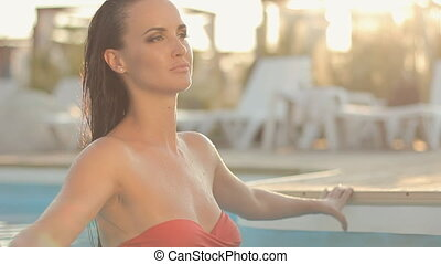 Sexual divine brunette with long wet hair in pink bikini...