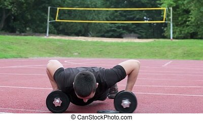 Teenager do push ups at outdoor on dumbbells