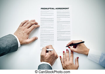 young man an woman signing a prenuptial agreement - closeup...