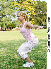 squats - a woman doing squats in park