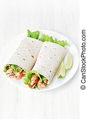 Wrap sandwiches with chicken and vegetables on white table,...